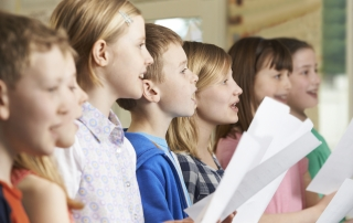 Group Of School Children Singing In School Choir ** Note: Shallow depth of field